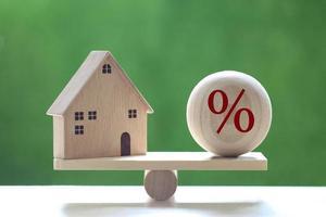 Modellhaus mit einem prozentualen Symbolsymbol auf einer Holzskala auf einem natürlichen grünen Hintergrund, Zinserhöhung und Bankkonzept foto