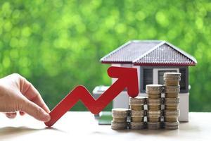 eine Frauenhand, die einen roten Pfeil auf einem Stapel von Geldmünzen mit einem Modellhaus auf einem natürlichen grünen Hintergrund, Geschäftsinvestition und Immobilienkonzept hält