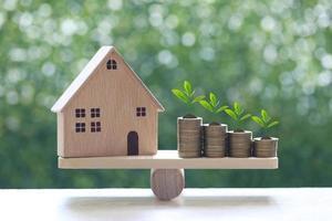Modellhaus mit Pflanzen, die auf einem Stapel Münzen auf einer Holzwippe mit einem natürlichen grünen Hintergrund, Geschäftsinvestition und Immobilienkonzept wachsen