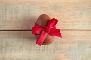 Schokoladenei mit rotem Band auf einem hölzernen Hintergrund. foto