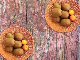 Kiwis und Aprikosen in zwei Weidenkörben auf einem hölzernen Tischhintergrund foto