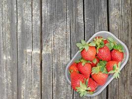 Erdbeeren in einem Plastikkorb auf einem hölzernen Tischhintergrund foto
