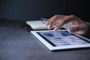 Männerhand, die an digitalem Tablett am Schreibtisch arbeitet