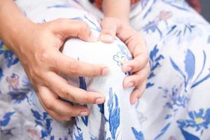 Nahaufnahme von Frauen, die das Knie vor Schmerzen halten foto