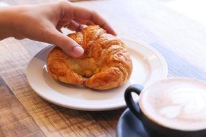 Frauenhand hält ein Croissant