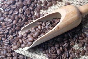 Draufsicht der frischen Kaffeebohnen im Holzlöffel auf Tisch foto