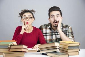 junge männliche und weibliche Studenten, die mit vielen Büchern sitzen und sich auf den Unterricht vorbereiten foto