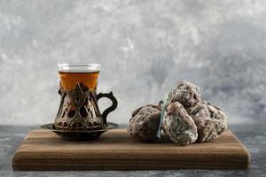eine Tasse heißen Tee mit getrockneter Persimone auf einem Holzbrett foto