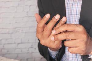 Mann mit Schmerzen in den Fingern schließen