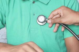 Arzt, der ein Stethoskop auf Person verwendet, die grünes Hemd trägt foto
