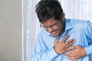 Mann im blauen Hemd hält Brust im Schmerz