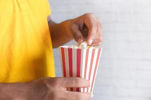 Mann im gelben Hemd, das Popcorn isst foto