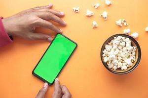 Mann, der Smartphone benutzt und Popcorn auf orange Hintergrund isst foto