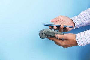 Mann, der Telefon benutzt, um auf blauem Hintergrund zu bezahlen