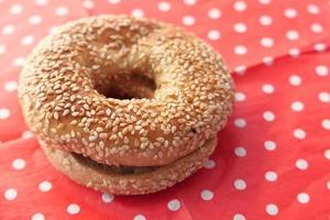 frischer Bagel mit Sesam auf Tupfen Tischdecke