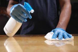 Person, die Handschuhe trägt, die eine Oberfläche reinigen