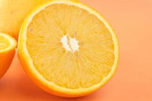 Nahaufnahme der Scheibe Orangenfrucht auf orange Hintergrund foto
