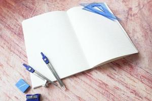 offenes Notizbuch mit Schulmaterial