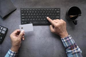 Draufsicht des Mannes, der Kreditkartendetails auf Computer eingibt