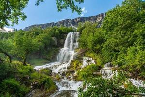Wunderschöner Wasserfall, der in Norwegen einen Berghang hinunterspült foto
