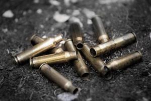 Haufen gebrauchter Munitionspatronen auf dem Boden foto