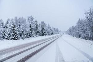 Winterstraße vorbei an einem Wald mit schneebedeckten Bäumen