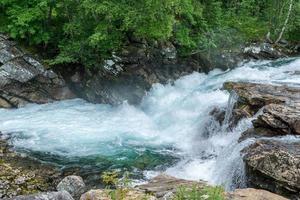 Bach in Norwegen mit frischem türkisfarbenem Wasser, das durch Felsen spült foto