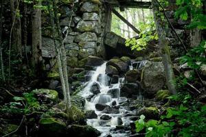 kleiner Wasserfall mit Wasser aus einer Mauer aus hundert Jahre alten Eisenhütten in Schweden