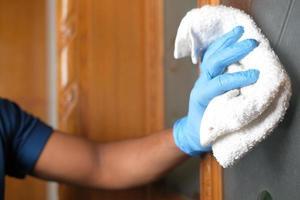 Person, die eine Oberfläche mit Handschuhen desinfiziert foto