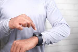 Mann trägt intelligente Uhr foto