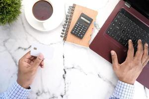 Person, die weiße Kreditkarte verwendet, um online einzukaufen