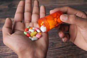 Hand hält viele bunte Pillen