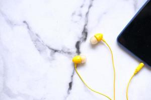 gelbe Ohrhörer an Smartphone angeschlossen