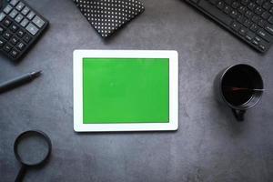 flache Zusammensetzung der digitalen Tablette auf dunklem Bürohintergrund foto
