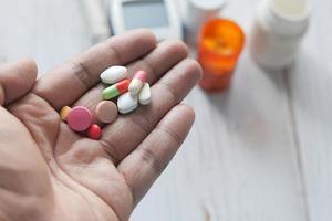Hand, die bunte Pillen auf neutralem Hintergrund hält