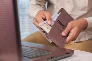 Mann, der Geld aus brauner Brieftasche nimmt