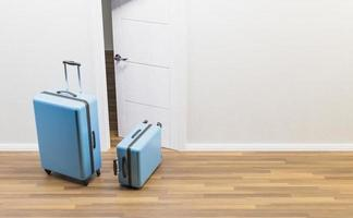 blaue Koffer vor einer offenen Tür foto