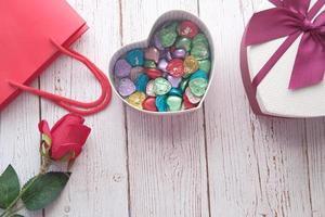 herzförmige Geschenkbox mit Süßigkeiten auf dem Tisch foto