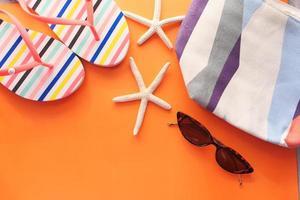 flache Zusammensetzung von Sommerstrandzubehör auf orangefarbenem Hintergrund
