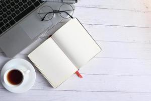 Kaffee, leeres Notizbuch und Kreisgläser