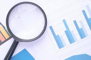Finanzdiagramm und Lupe auf dem Tisch foto