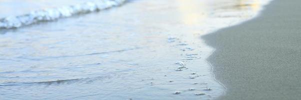 verschwommene Welle des Meeres am abendlichen Sandstrand