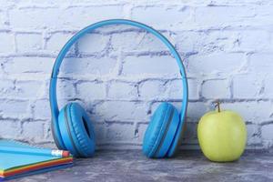 Hörbuchkonzept mit Kopfhörern und einem Apfel