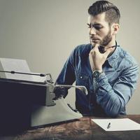 junger Mann mit Bart und Schnurrbart an der Schreibmaschine, die seine Pfeife raucht foto