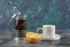 eine weiße Keramik Tasse Getränk mit einer Teekanne auf einem Marmorhintergrund foto