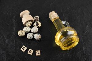 frische Bauernwachteleier und Olivenöl mit Holzklötzen mit dem Wort Ei auf einem schwarzen Hintergrund
