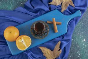 Glas Tee, Orange und Zimtstangen auf einem blauen Brett foto