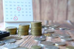Stapel von Münzen und Kalender auf hölzernem Hintergrund