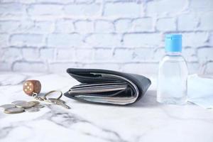 eine Brieftasche, ein Händedesinfektionsmittel, Schlüssel und Münzen auf dem Tisch