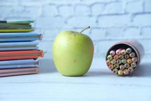 Zurück zum Schulkonzept mit Apfel und Bleistiften auf dem Tisch